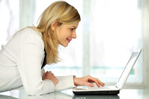 woman smiling and looking at laptop computer