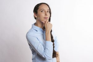 woman with braided hair and blue shirt thinking