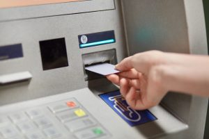 person inserting debit card into ATM