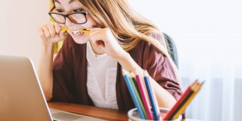 young woman in front of laptop stress-fully biting pencil