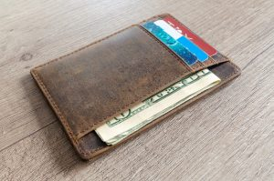 old brown leather wallet with American cash and credit and debit cards