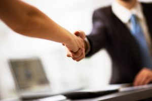 man in suit shaking hands with a woman