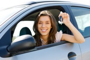 woman in silver car smiling and holding out keys