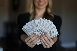 woman smiling and holding out many one hundred dollar bills