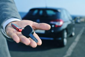 man in suit offering a car key to the observer, with a car in th