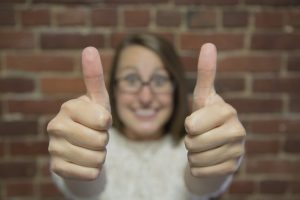 excited woman with light brown hair showing two thumbs up