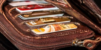 brown wallet full of credit and debit cards